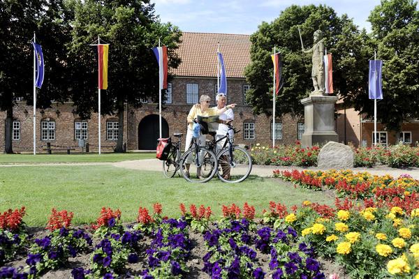 Fahrradfahrer am Roland vor dem Schloss-Torhaus